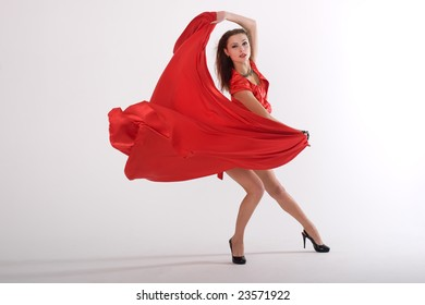 sexy lady in red dress in studio is dancing