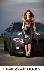 Sexy lady with a sport car at night