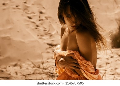 Sexy lady take off a dress and looks at the camera in a desert