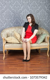 sexy lady wearing red dress and black jacket rests on a sofa