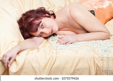 Sexy lass in peach-coloured combinations with pearl beads is lying on a bed