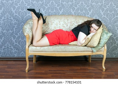 sexy lass wearing red dress is lying on a sofa