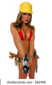 Sexy latino female construction worker in bikini, hardhat and tool belt pointing a cordless screw gun / drill at the camera.