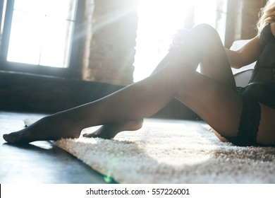Sexy legs. Close up of young woman touching her legs in black hosiery on the carpet at home