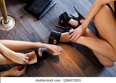 Sexy legs and feet with high heels black shoes. Sexy stripper girls touching feet before strip tease. Sexy attractive models with long legs and beautiful hands, with black and transparent nail polish