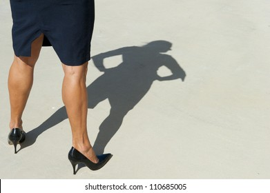 Sexy legs and isolated shadow on concrete floor of confident woman in dominant pose.
