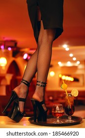 Sexy legs of a waitress standing on the bar with a cocktail. Copy-space. Indoor shot