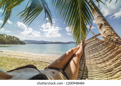 Sexy legs of a woman lying in a hammock on a beach by the open sea