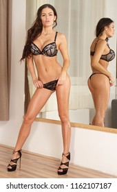 Sexy lingerie fitness ethnic woman in black lace in front of mir