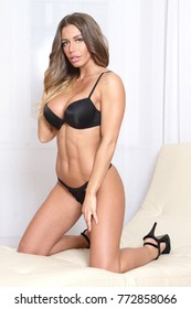 Sexy lingerie girl with muscular abs and body in black bra