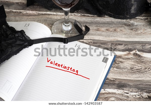 Sexy lingerie, wine glass and a calendar with the German word for Valentine's Day