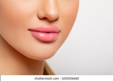 Sexy Lips. Part of Face, Young Woman close up. Perfect plump Lips bodily Lipstick. Beautiful Lips Close-up. Makeup. Peach Color of Lipstick on Large Lips. Botox. Perfect Makeup.