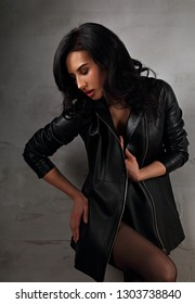 Sexy long black hairstyle woman posing in fashion black leather jacket and trendy tights on studio background. Closeup portrait