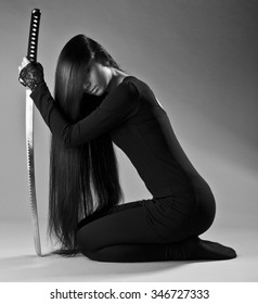 Sexy long haired ninja girl or assassin woman kneeling and holding katana sword in hand. La femme fatale
