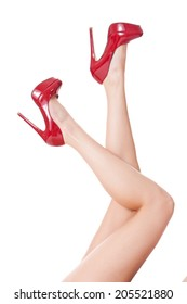 Sexy long shapely bare female legs in elegant red stilettos kicking tantalizingly in the air in a provocative gesture, isolated on white