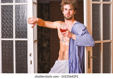 Sexy lover concept. Bachelor sexy body chest and belly. Sexy attractive macho tousled hair coming out through bedroom door. Guy shimmering sweaty skin wear bathrobe. Man with sexy torso drink wine.