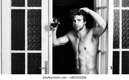 Sexy lover concept. Guy smooth skin posing seductive. Beginning great evening. Man with sexy torso drink wine. Sexy attractive macho tousled hair coming out through bedroom door. Bachelor sexy body.
