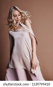 Sexy luxurious woman in a dress. Autumn collection of women clothing. Fashion blonde in a long beautiful dress posing on background. Beautiful hair and a perfect girl figure
