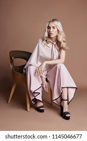 Sexy luxurious woman in a dress sitting on a chair. Autumn collection of women clothing. Fashion blonde in a long beautiful dress posing on background. Beautiful hair and a perfect girl figure