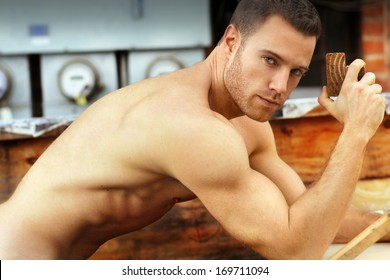 Sexy macho guy shirtless holding working with wood