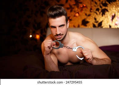 Sexy macho man with handcuffs laying on bed, bdsm