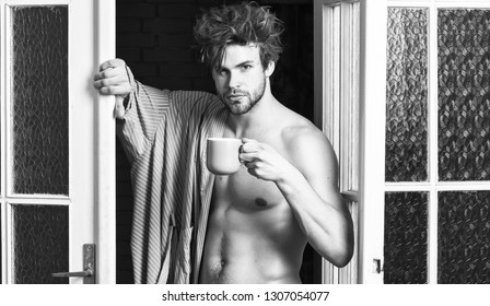 Sexy macho tousled hair coming out bedroom door. Man lover near door. Sexy bachelor lover concept. That was great night. Guy attractive lover enjoy morning coffee. Seductive lover full of desire.