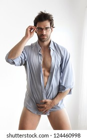 Sexy male model with hot naked body wrapped in business shirt wearing eyeglasses