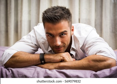 Sexy male model lying alone on his bed in his bedroom, looking at camera with a seductive attitude