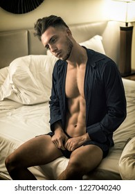 Sexy male model sitting alone on bed in his bedroom, looking at camera with a seductive attitude,, with shirt open on muscular chest and torso
