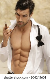 Sexy male model smoking cigar in open formal attire exposing great toned muscular body and abs