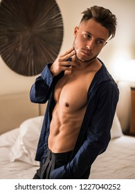 Sexy male model standing alone on bed in his bedroom, looking at camera with a seductive attitude,, with shirt open on muscular chest and torso