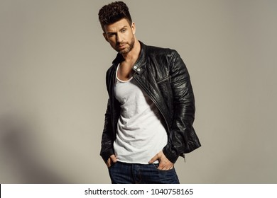 Sexy male model wearing leather jacket isolated on grey background
