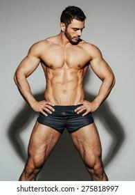Sexy male muscular model in black swimwear looking down