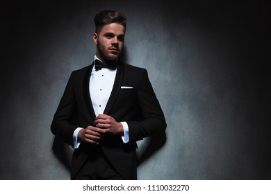 sexy man in black tuxedo holding hands together while looking to side and leaning against a dark grey wallpaper