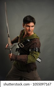 The sexy man is dressed in a Robin Hood type costume holding a sword.