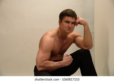 the sexy man is flexing his arms while seated.