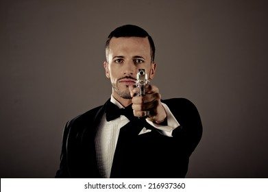 Sexy man gangster agent criminal police in a tuxedo pointing a gun