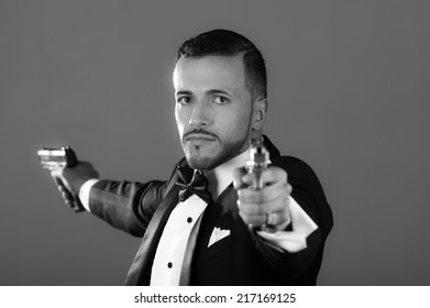 Sexy man gangster agent criminal police in a tuxedo pointing two guns black and white portrait