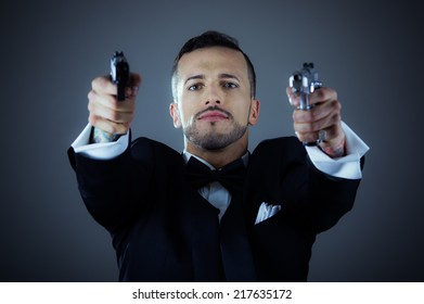 Sexy man gangster agent criminal police in a tuxedo pointing two guns