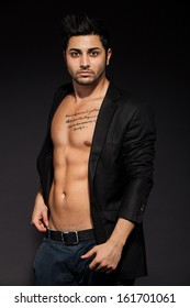 Sexy man with great abs over black isolated background wearing sunglasses