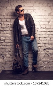 Sexy man with handbag. Standing in black leather jacket and jeans