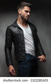 sexy man in leather jacket showing how much weight he lost by pulling pants with his finger in studio