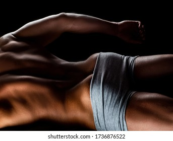 Sexy man with muscular body and bare torso. Muscular butt. Back view of a muscular man posing on black background