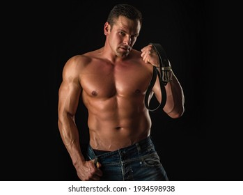 Sexy man with muscular body and bare torso. Male holding leather belt