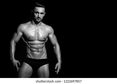 sexy man. sexy man with muscular body and strong torso of bearded bodybuilder athlete in underwear pants posing with bare chest and belly on black background, sport and training, copy space