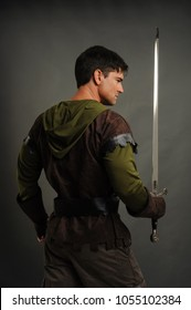The sexy man is in a new age style costume holding a sword.
