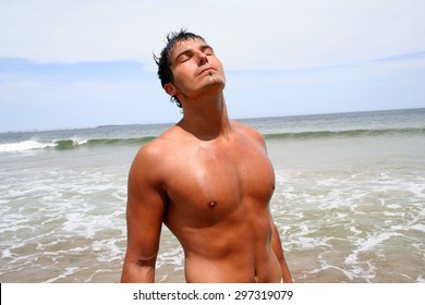 Sexy man on the beach enjoying summer