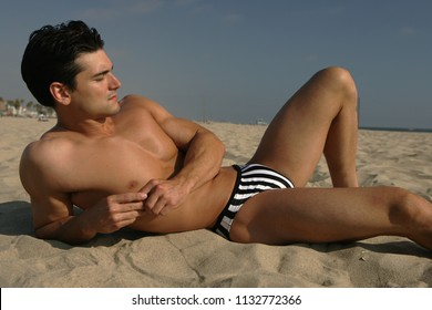 The sexy man poses at the beach.