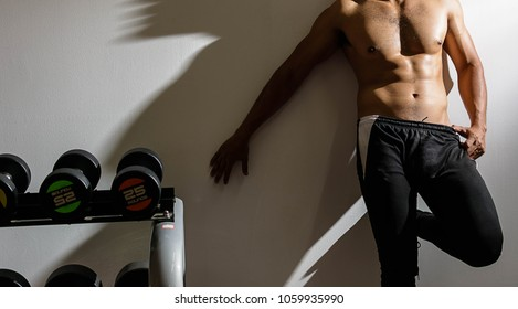 Sexy man  posing muscular body in the gym with exercise equipment over white wall. Can used for concepts of diet to bodybuilding and fitness for healthy. Copy space for text.