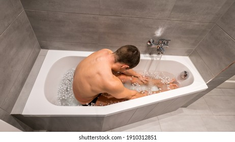 Sexy man sitting in a bathtub filled with cold water and ice cubes for recovery and health purposes